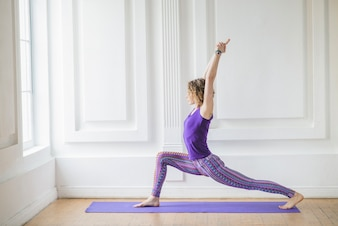 Donna che si estende e fa yoga a casa