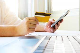 Donna che utilizza il cellulare per lo shopping online e paga per credito ca