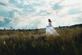 Donna con abito da sposa camminare su un prato