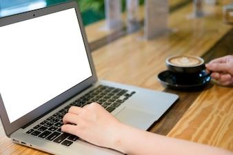 Donna con computer portatile nel negozio di caffè