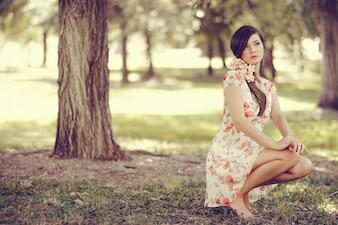 Donna con i fiori nei capelli pensando nel parco