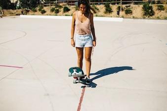 Donna con skateboard guardando verso il basso