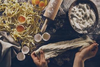 Donna cuocere le mani preparando fare gustosa pasta casalinga classica italiana sul tavolo di legno. Avvicinamento. Vista dall'alto. Tonificante.