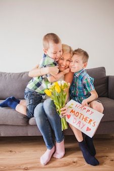 Donna felice ridendo con i suoi figli e festeggiando la madre