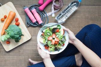 Donna in sportwear in possesso di un piatto di insalata fresca con fragole e kiwi, stile di vita sano