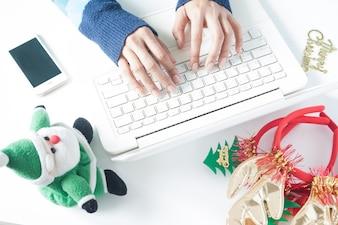 Donna mani digitando sul computer portatile della tastiera, utilizzando smartphone con decorazioni natalizie, shopping online