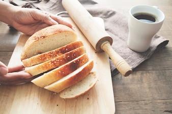 Donna mano che tiene pagnotta di pane sulla piastra in legno con utensili da cucina e tazza di caffè