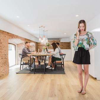 Donna parlando telefono in piedi alla scrivania in ufficio