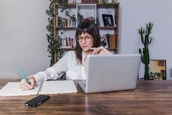 Donna seduta a tavola con computer portatile e prendere appunti