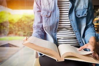 Donna seduta in un caffè, lettura libro