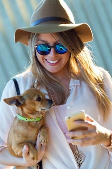Donna sorridente con il cane e il telefono