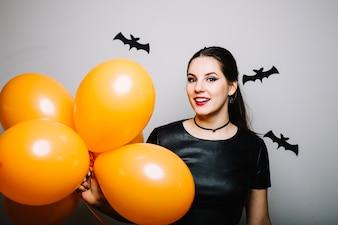 Donna sorridente con palloncini a pipistrelli