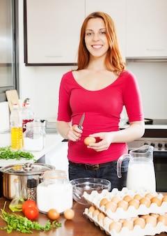 Donna sorridente in rosso fare omelette con le uova