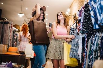 Donne sorridenti che scelgono i vestiti