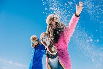Due amiche si divertono e godono la neve fresca in una bellissima giornata invernale in montagna