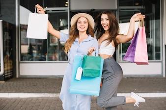 Due donne che presentano con i sacchetti di carta