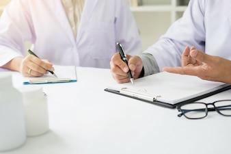 Due medici che discutono le note del paziente in un ufficio che punta ad un appunti con documenti mentre effettuano una diagnosi o decidono sul trattamento