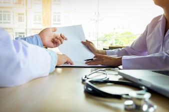 Due medici che discutono le note del paziente in un ufficio che punta ad un appunti con documenti mentre fanno una diagnosi o decidono sul trattamento