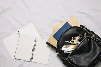 Due neti libri e borsa con forniture per ufficio