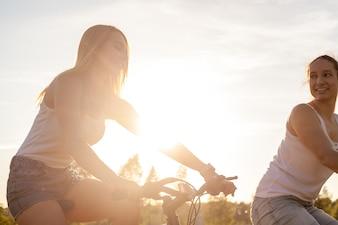 Due ragazze in bicicletta al tramonto