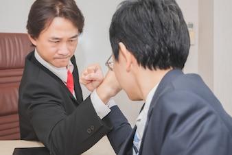 Due uomini d'affari che corrono in lotta di braccio