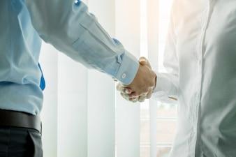 Due uomini d'affari fiduciosi stringendo la mano durante una riunione in ufficio, il successo, il commercio, il saluto e il concetto di partner.