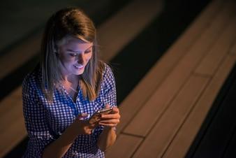 Felice donna di bellezza leggendo buone notizie su smartphone