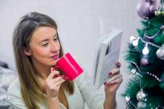Felice giovane donna leggendo il libro di fronte all'albero di Natale. Serata di Natale. Giovane bella donna bionda leggere il libro in appartamenti classici, albero decorato.
