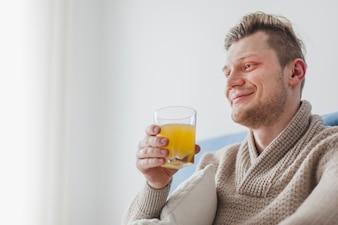 Felice l'uomo in possesso di un bicchiere di succo d'arancia