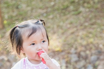 Felice Little asian girl mangiare fragola di gelatina nel parco