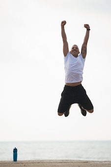 Felice uomo potente con le braccia alzate saltando