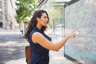 Fiduciosa giovane donna in piedi alla mappa all'aperto