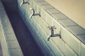 Fila di rubinetti in acciaio in un grande bagno