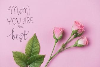 Fiori decorativi e foglie sulla superficie rosa per la festa della mamma