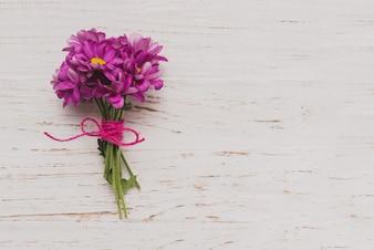 Fiori viola legato sulla superficie di legno bianco