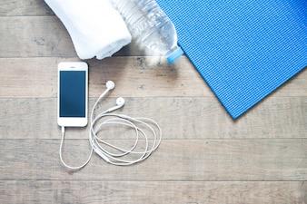Flat lay di telefono cellulare con auricolare e stuoia di yoga, asciugamano e bottiglia di acqua sul pavimento di legno, spazio di copia