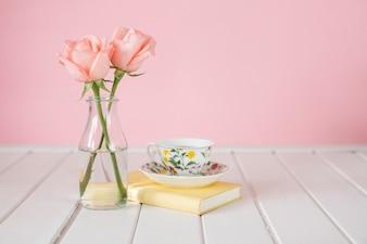 Fondo in legno con il vaso, tazza di caffè e libro