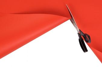 Forbici che tagliano carta sfondo rosso