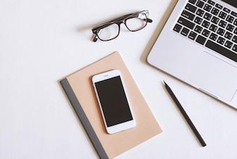 Foto piatta della scrivania con laptop, smartphone, occhiali da vista e notebook con sfondo di spazio di copia