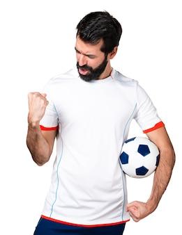 Giocatore di football americano fortunato che tiene una pallina da calcio