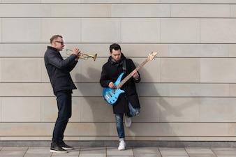 Giocatore di tromba e chitarrista che gioca davanti alla parete