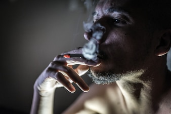 Giovane adulto che fuma in camera oscura.