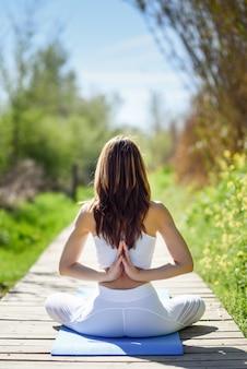 Giovane bella donna facendo yoga in natura
