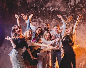 Giovane celebrazione di amici con le mani in su