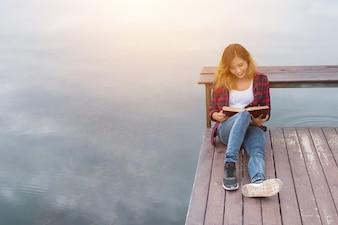 Giovane donna bella, pantaloni a vita bassa rilassante seduta sul molo lettura b