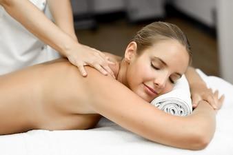 Giovane donna bionda con massaggio e sorridere in spa