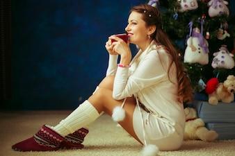 Giovane donna graziosa sotto albero di nuovo anno