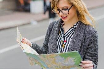 Giovane donna in piedi con la mappa