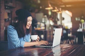 Giovane e bella donna pantaloni a vita bassa che si siede in un caffè, rilassarsi un