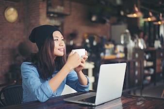Giovane e bella donna pantaloni a vita bassa che si siede in un caffè, tenendo